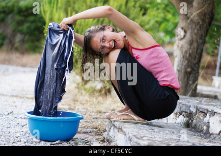 Greece, Ionian Islands, Ithaca, Woman washing clothes, smiling, portrait - Stock Photo