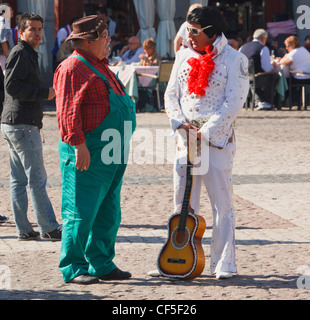 Madrid, Spain. Elvis Presley impersonator talking with another busker in the Plaza Mayor. - Stock Photo