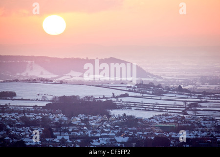 View over Glastonbury town covered in snow, from the top of the Tor at sunset. - Stock Photo