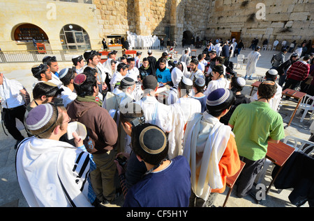Crowds worship at the Western Wall, the holiest site in Judaism outside the Temple Mount itself in Jerusalem, Israel. - Stock Photo