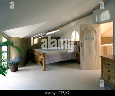 The interiof two storey Eco house in the Cambridgeshire Fens, UK, showing bedroom wooden bed and chest of drawers, - Stock Photo
