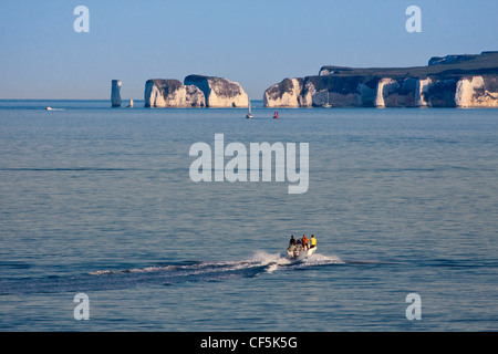 People aboard a speed boat heading towards Old Harry Rocks, two chalk sea stacks on the Isle of Purbeck. - Stock Photo