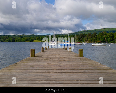 View along a wooden jetty towards boats moored on Lake Windermere at Waterhead. - Stock Photo