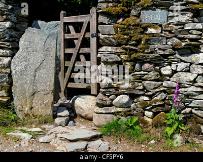Sign showing the direction to Rydal beside a gate in a drystone wall. - Stock Photo