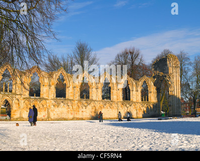 People walking through snow in the Yorkshire Museum Gardens by the ruins of St Mary's Abbey Church. - Stock Photo