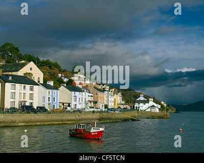 Dark clouds gather over a fishing boat in Aberdovey Harbour within Snowdonia National Park. - Stock Photo