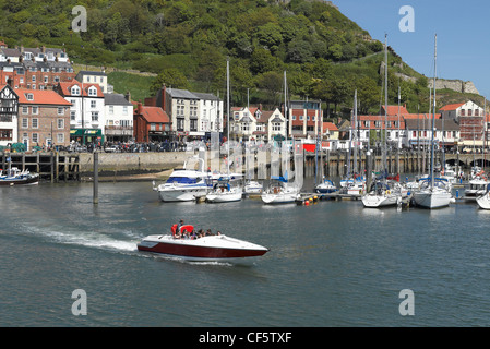 Tourists in a speedboat leaving Scarborough Harbour. - Stock Photo