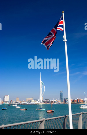 A Union Jack flag flying on the waterfront at Gosport opposite the 170m high Spinnaker Tower at Gunwharf Quays in - Stock Photo
