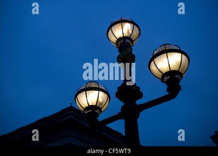 An illuminated street light outside the British Museum at night. - Stock Photo