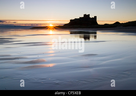 The outline of Bamburgh Castle against the sunrise. In the Wars of the Roses, Bamburgh was held by the Lancastrians - Stock Photo
