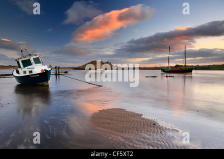 An old fishing boat moored in Alnmouth estuary at low tide. - Stock Photo