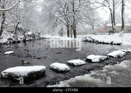 Stepping stones covered in snow leading across a river.