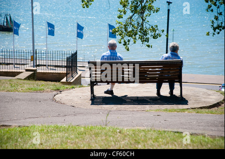 An elderly couple sitting on a bench looking out to sea at Southend-on-Sea. - Stock Photo