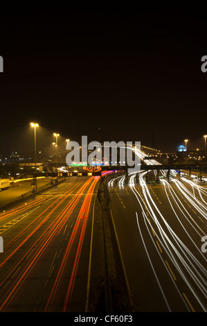 Light trails from vehicles travelling to and from the Dartford River Crossing at night. - Stock Photo