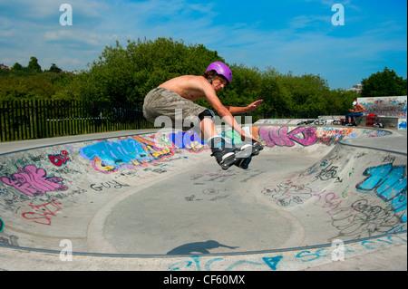 Teenage rollerblader (in-line skater) performing stunts at a purpose built skatepark. - Stock Photo