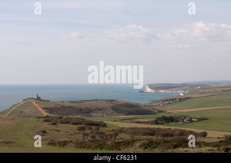 A view from Beachy Head looking west along the coast with the Belle Tout Lighthouse seen in the distance. - Stock Photo