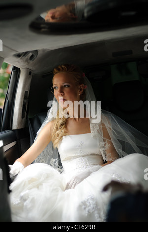 Bride in wedding dress sits in limousine and looks out in window. - Stock Photo