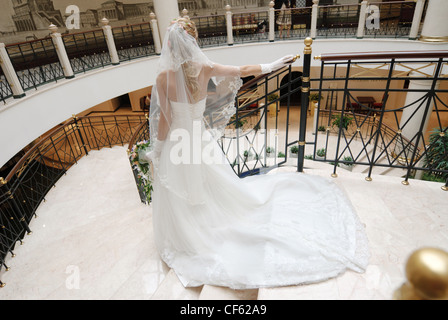 Bride in beautiful wedding dress stands on broad staircase, rear view. - Stock Photo