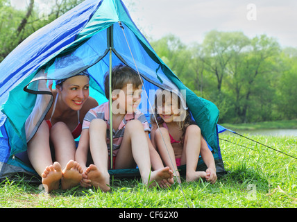Happy mother and her kids in swimsuit sit in blue tent on bank of river in green forest - Stock Photo