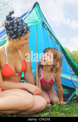Happy mother and her little daughter sitting near blue tent on green grass - Stock Photo