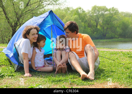 Happy family - mother, father, little girl and boy - sitting in blue tent on green lawn on bank of river at sunny - Stock Photo