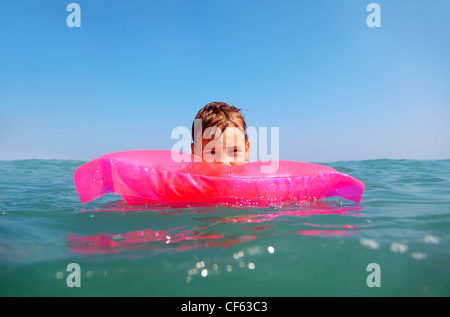 The little boy floating in sea on inflatable pink matrese. shot from underwater box, water on box blurry - Stock Photo
