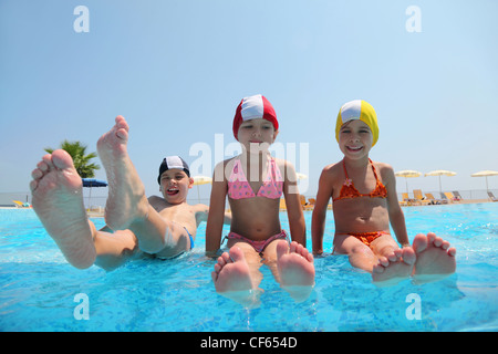 Two girls sit on skirting in  pool and feet overwater and boy lift which falls in water, underwater package shot - Stock Photo