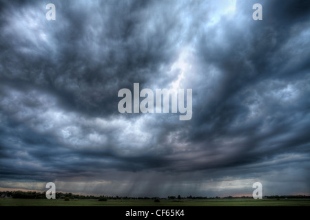 Rain falling from summer storm clouds over distant fields. - Stock Photo