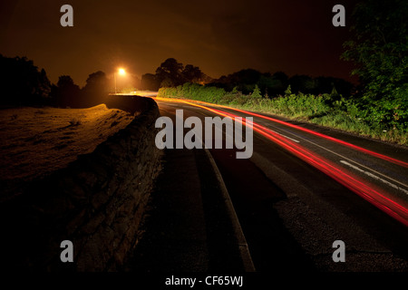 Light trail from a car travelling along a rural road at night. - Stock Photo