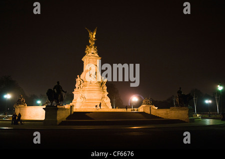 The Victoria Memorial lit-up in Queen's Gardens in front of Buckingham Palace at night. - Stock Photo