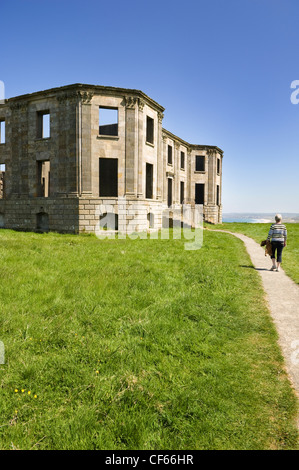 A woman walking along a path leading to the remains of Downhill House. - Stock Photo