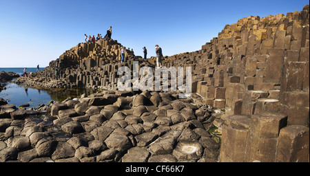 Tourists exploring the interlocking basalt columns of the Giants Causeway,  a World Heritage Site and National Nature - Stock Photo