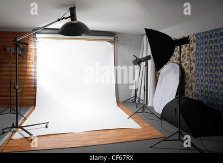 White background inside studio - dark room lighted big lamps and spotlights - Stock Photo
