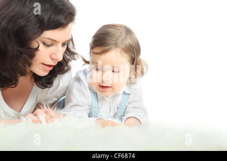 Thoughtful mother and her little daughter lie on white fluffy rug - Stock Photo