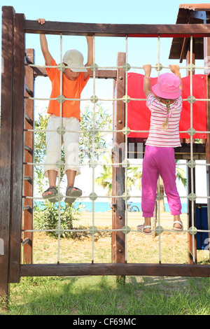little boy and girl climbing on rope ladder at playground, sunny day, sea - Stock Photo