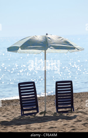 Two dark blue plastic chairs stand in kontrazhure on  beach, near water under  large blue umbrella - Stock Photo