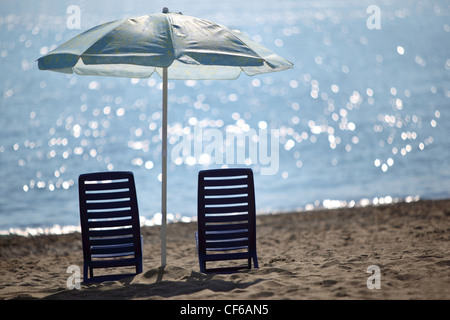 Two dark blue empty chairs  stand on  beach near  sea under shade of large umbrella - Stock Photo