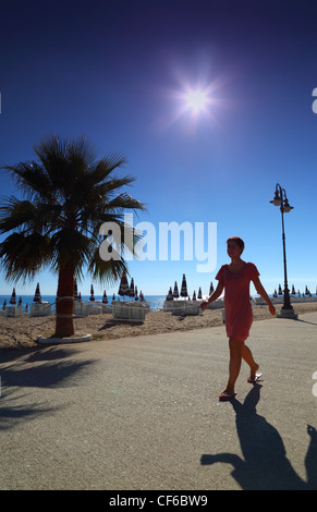 Girl goes on path with palms on empty sandy beach with folded umbrellas and sunbeds, burning sun and cloudless sky - Stock Photo