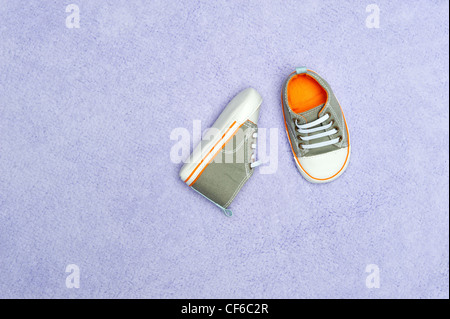 A pair of new baby boy tennis shoes on a purple blanket - Stock Photo