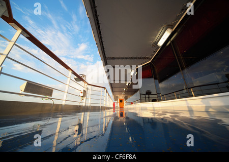 deck of cruise ship in morning shining by light of rising sun. reflection in deck - Stock Photo
