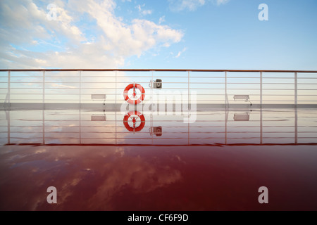 saving buoy in deck of cruise ship. deck shining by morning sun. reflection in deck - Stock Photo