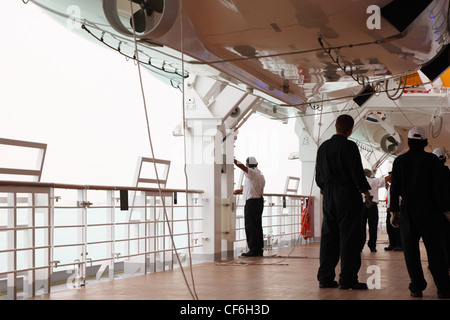 service staff in black uniform standing on cruise liner deck, view from back - Stock Photo