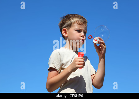 Boy stands straight and inflates soap bubbles in summer - Stock Photo