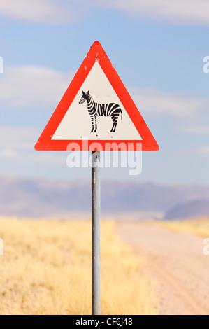 Zebra crossing sign along a gravel road. Namibia - Stock Photo