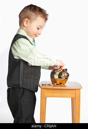 A Young Boy Wearing A Suit Putting Money In His Piggy Bank; Edmonton Alberta Canada - Stock Photo