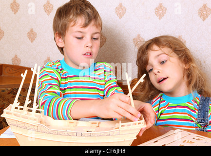 Blonde boy and girl in striped shirt make homemade wooden boat - Stock Photo