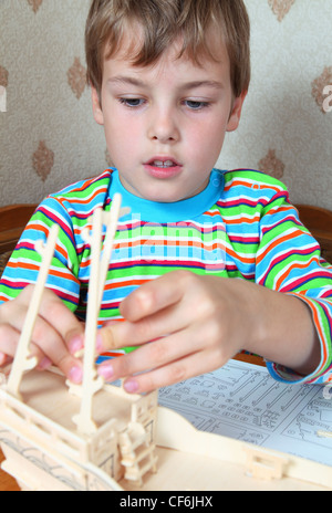 Zealous blonde boy in striped shirt make homemade wooden boat - Stock Photo