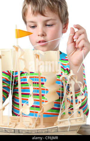 Small boy in striped shirt works with zeal on artificial ship, he pulls the sail - Stock Photo