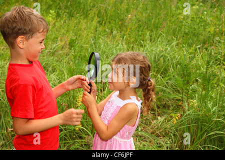 little brother and sister play with big black loop in nature - Stock Photo