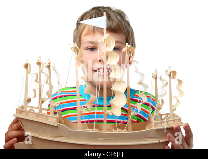 Small boy in striped shirt holds artificial wooden ship with paper sails - Stock Photo